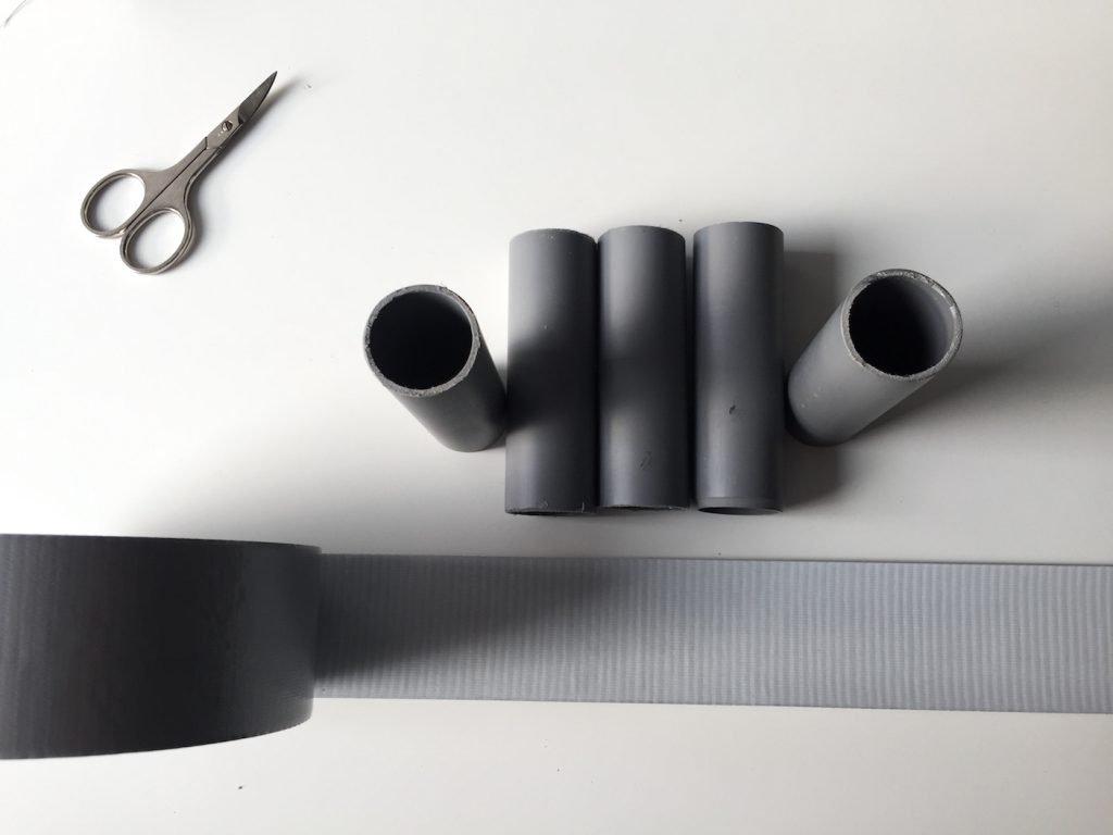 PVC-Rohre Klebeband und Schere auf weißem Tisch